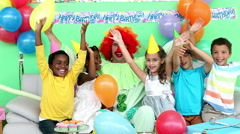 Cute children celebrating a birthday with a clown Stock Footage
