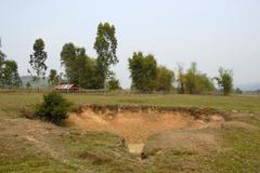 large bomb crater from the 2nd indo-china war, vietnam war, near phonsavan, p - stock photo