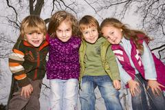 a group of young children of ages 4, 4, 3 and 4, outdoors - stock photo