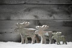 Three wooden elk or reindeers on a grey background - christmas decoration Stock Photos