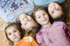 Group of four little girls lying on the floor, from the left 6, 11, 9 and 10  Stock Photos