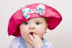 Stock Photo of baby girl, 7 months, wearing a hat