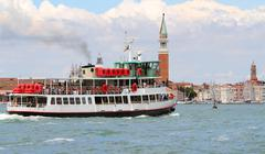 Stock Photo of boat ferry for transporting tourists in venice and saint george bell tower