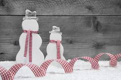 christmas snowmen with snow and ribbon on grey wooden background. - stock photo