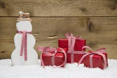 three red christmas presents and snowman with snow on wooden background - stock photo