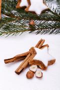 Star-shaped cinnamon cookies with fir branches, cinnamon sticks and hazlenuts Stock Photos