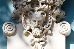 horned head of satyr,old house decoration, greek mythology - stock photo