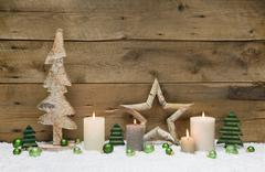 wood christmas decoration with green balls, candles and stars on wooden backg - stock photo