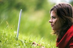 a beutiful student girl working on her laptop outdoor at sunny day - stock photo