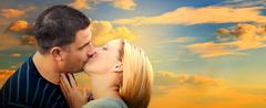 Couple kissing in romantic love scenery on sunset sky. panorama version Stock Photos