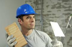 workman wearing a hard hat, holding a brick trowel and a brick - stock photo