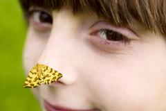 Ten year old girl with a speckled yellow (pseudopanthera macularia) moth on h Stock Photos