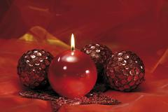 red ball-shaped candle with red christmas tree balls on red velvet - stock photo