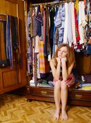 Girl sitting in wardrobe deliberating what to wear - stock photo