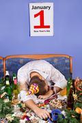 New year's celebration - drunk man sleeping on the table Stock Photos