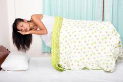 levitating girl sleeping in bed - stock photo