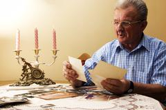 Senior man looking at old photographs. reminisce about the past Stock Photos