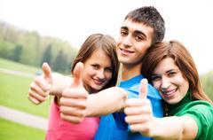 Three young happy friends laughing and giving okey sing Stock Photos