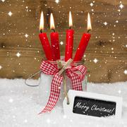 snowy merry christmas: four red burning candles with bow and message on snowy - stock illustration