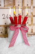 christmas eve: four red burning candles with a shabby white advent calendar b - stock photo