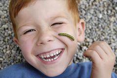 child with a caterpillar on the face exploring the nature nature games - stock photo
