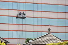 Window cleaner at multistory building in semerang, central-java, borneo, indo Stock Photos