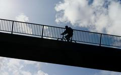 cyclist riding his bike up a bridge, with cloudy sky in the background, compo - stock photo