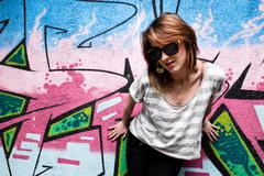 Stylish fashionable girl portrait against colorful graffiti wall. fashion, tr Stock Photos