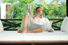 young man relaxing with drink on gazebo bed in garden NTSC - stock footage