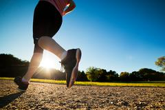 Young fit woman does running, jogging training in a park at summer sunny day. Stock Photos