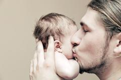 Father with his young baby cuddling and kissing him on cheek. parenthood, lov Stock Photos