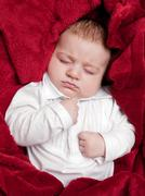 Lovely 3 months baby sleeping on bed covered with red soft blanket Stock Photos