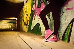 Stock Photo of close up of pink sneakers worn by a teenager. grunge graffiti wall, retro vin