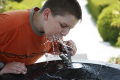 12-year-old boy drinks water Kuvituskuvat