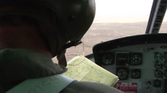 Helicopter pilot reads map while flying Stock Footage