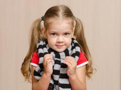 the three-year girl in a diseased warm scarf - stock photo