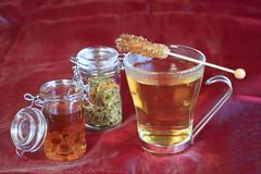 Stock Photo of a cup of tea with a lockable glas of rock candy in rum and tea in a glas