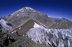 Female climber near a penitentes field with aconcagua westface in the backgro Stock Photos