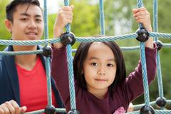 asian dad and daughter on playground - stock photo
