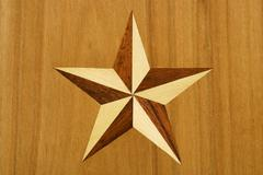 Stock Photo of intarsia, star out of nut tree and maple wood in cherrywood