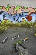 Empty color-cans in front of a concrete wall with colorfull graffitti Stock Photos