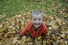 nine-year-old boy in the autumn foliage - stock photo