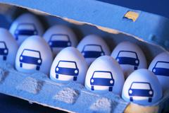 Eggs with pictures of car in an egg carton Stock Photos