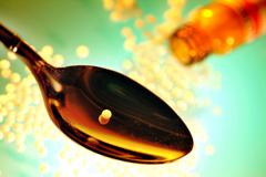 Stock Photo of homeopathic remedy, globule on a spoon, many globules and a medicin bottle in