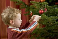 Stock Photo of a little boy is decorating the christmas tree