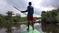 Amazon boy guides canoe toward landing  - stock footage