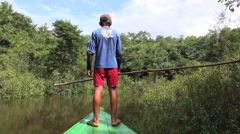 Amazon boy directs canoe  Stock Footage