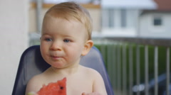 HD1080p25 Baby (10 months old) eating a watermelon on the balcony. Part 3. Stock Footage