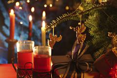 Hot drink, tea, grog, mulled wein with burning candels and gifts beneath a br Stock Photos