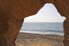 A rock gate at the beach ormos vlichada, vlichada, santorini, greece Stock Photos